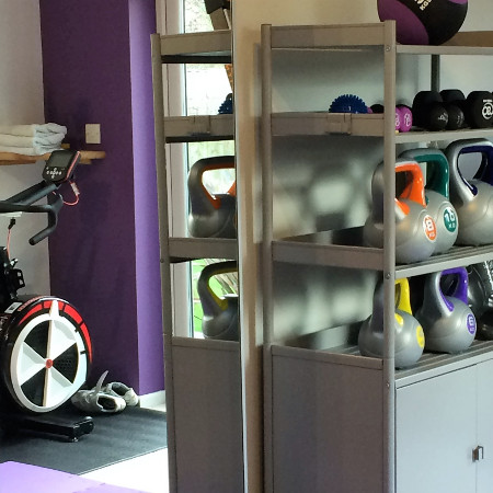 A variety of weights on shelves in a gym
