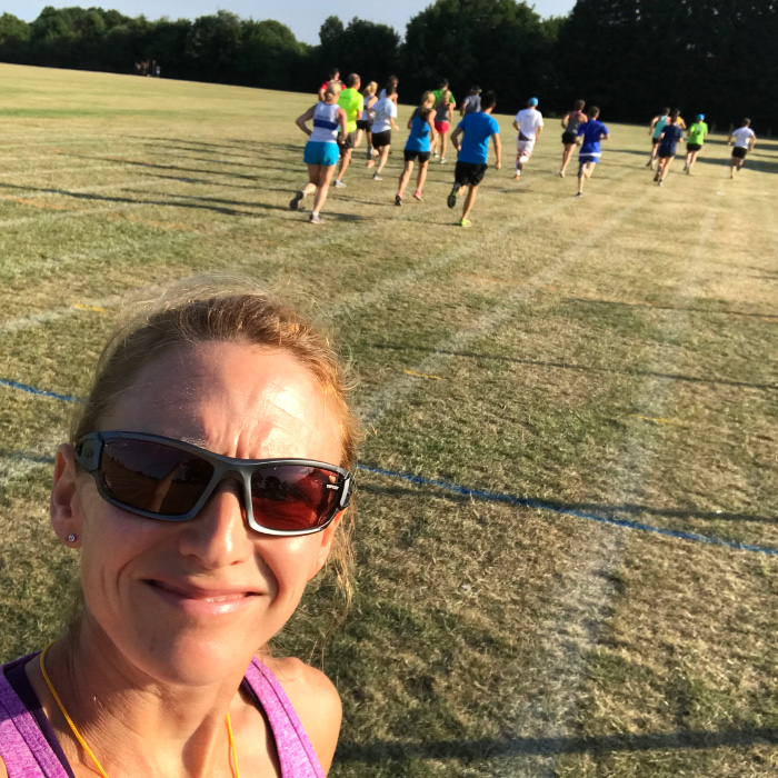 Selfie of a coach with her athletes running in the background