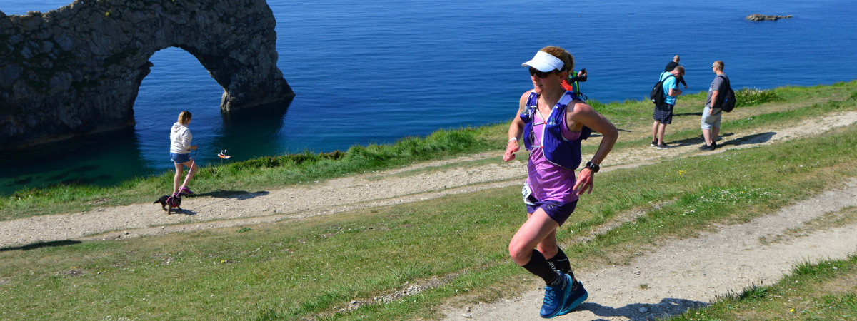 A runner competing in the Jurassic Quarter ultra running on the coastal path at Durdle Door