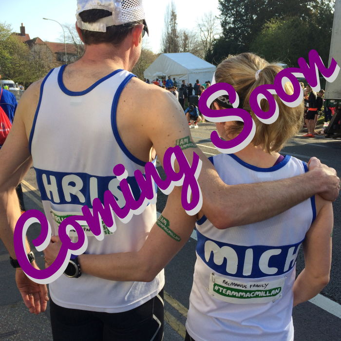 Photo of two runners with their arms round each other and their names on the back of their running vests